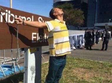 Pedindo cassação de Temer, manifestante se amarra à placa do TSE